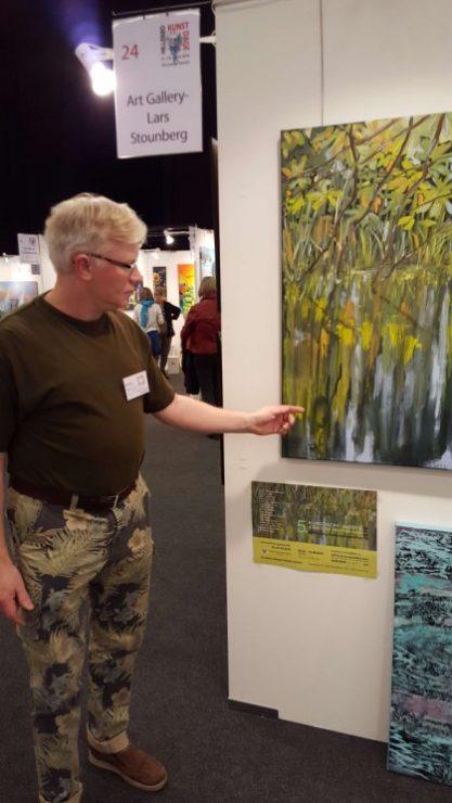 Lars Stounberg viser sit maleri Vandspejling sø